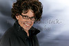 Middle Aged Woman with Curly Hair wearing eyeglasses and Smiling