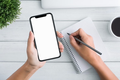 Woman hand holding blank smartphone and writing in notebook