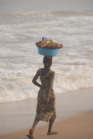 "This woman was carrying Kasava while walking on the beach near Elmina.  Kasava is a staple food of Ghana and is used primarily to make ""fufu'.  She will either bring it to market, or to her home for her personal use.  Walking along the beach is often easier, (and safer) than walking along the roadside where there are no sidewalks and the risk of being hit by a car or truck is high.  This beach is very close to Elmina Castle, a former slave fort and now a World Heritage Site."
