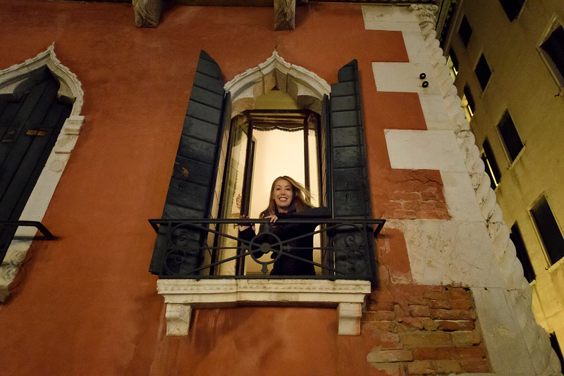 Woman leaning out the window of the Hotel Danieli near Piazza San Marco, Venice, Italy at night