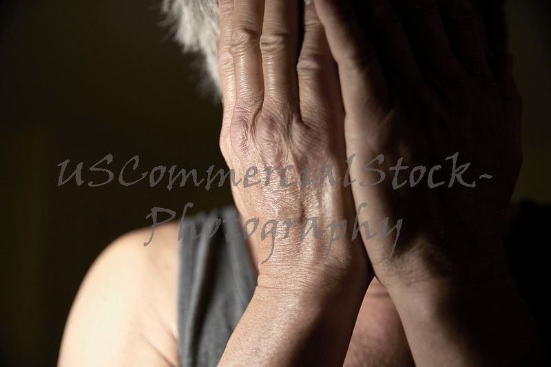 Man covering his face with his hands