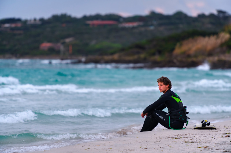 Waiting his turn to kite board on Spiaggia della Pelosetta, Sardinia, Italy