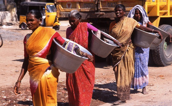 Many laborers in Soutern India are women.  These women  are carrying buckets which will be filled with sand and/or cement for building.  When filled, the buckets will be carried on their heads, and often they will have to climb a rudimentary ladder to get to  second or third story.  Women laborers get paid less than one half of what a male laborer would earn doing the same job.