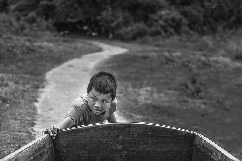 a boy helping his dad with their boat in Sangkhlaburi, Thailand
