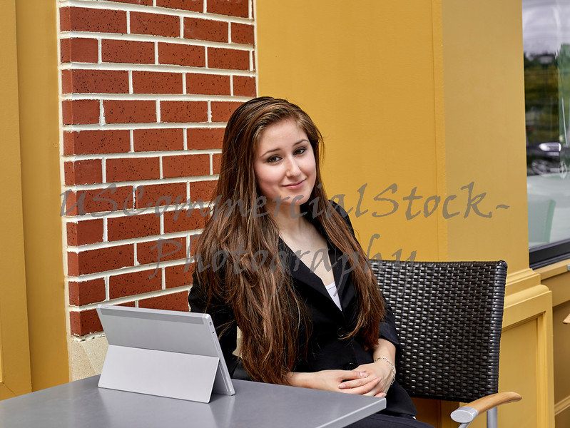 Young Woman Smiling and Sitting at Outdoor Cafe