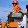Worker stands in aerial lift bucket