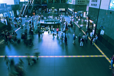 Wide angle view of busy train station looking down on commuters at Kyoto Station
