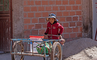 Uros boy bringing home a bucket of water and pots and pans for his family.