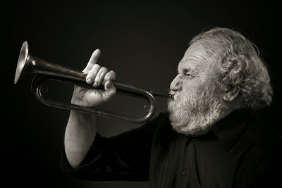 Old man with beard blowing hard on a bugle.