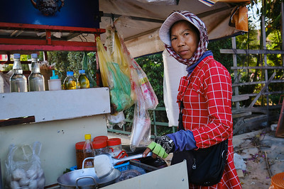 Street food shop keeper cooking food at her stall in Siem Reap, Cambodia.