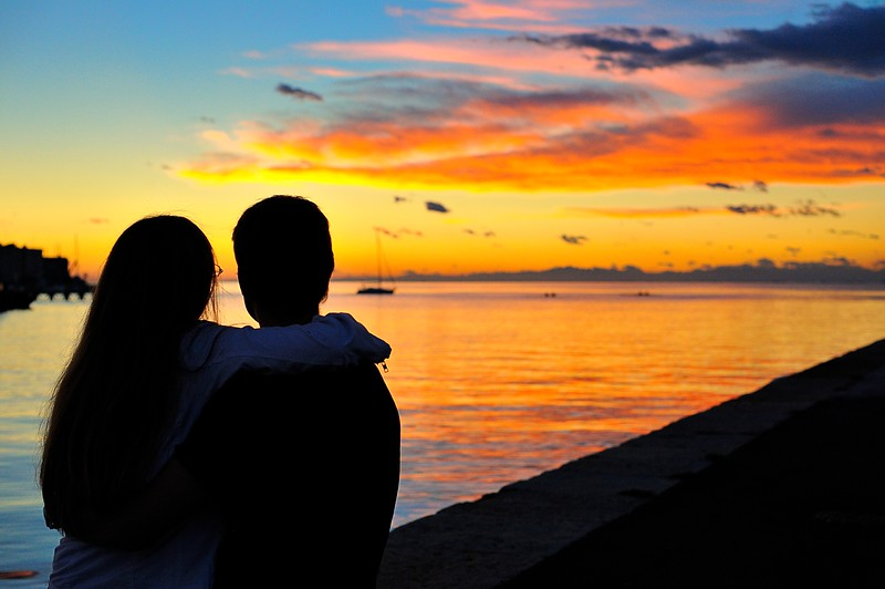 Couple Watching a Beautiful Sunset over Trieste Harbor, Italy