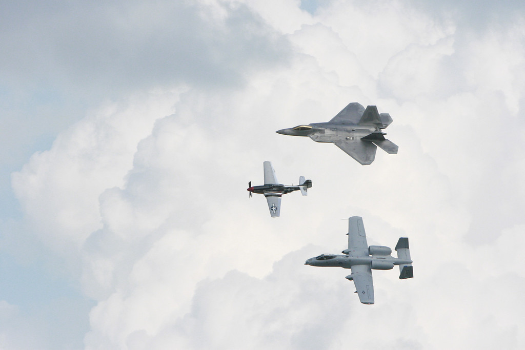 """During the day they had a few """"legacy flights"""" -- pairing today's airpower with its predecessors. Top to bottom, the F-22 Raptor, the P-51 Mustang (WWII, 150,000 were produced, 150 remain mostly in private collections) and the A-10 Thunderbolt/Warthog -- A Vietnam era aircraft that is still an active part of the airstrikes in Afghanistan and Iraq today. I have a special affection for the Warthog due to Iraq."""