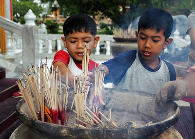 Boys offer incense at a Buddhist temple in Phuket, Thailand.
