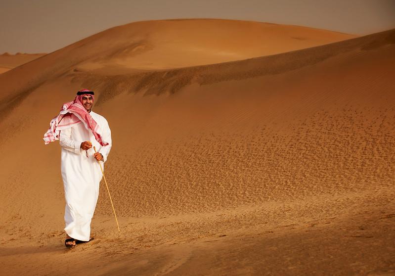 Kuwait - Man walking in sand dunes