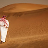 Kuwait - Man walking in sand dunes