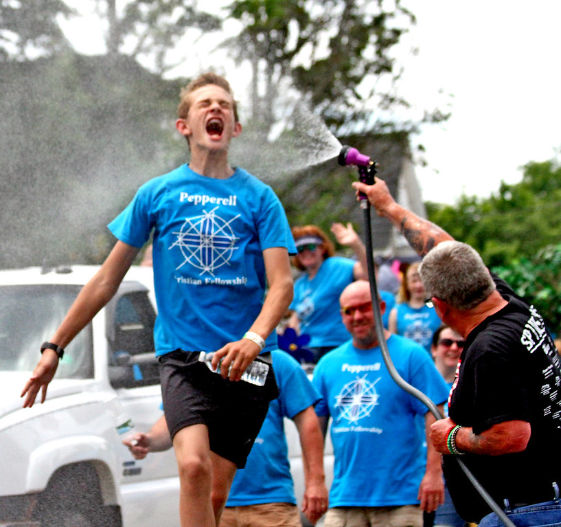 . Avery Burris, 13, a member of the Pepperell Christian Fellowship, gets a much needed cool down from Kevin Zappelli with his waterhose along the Pepperell 4th of July Parade. Nashoba Valley Voice Photo by David H. Brow