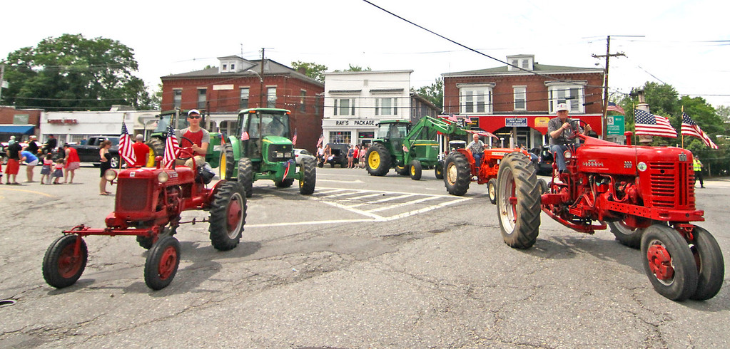 . A group of tractors drive through downtown Pepperell in the 4th of July Parade. Nashoba Valley Voice Photo by David H. Brow