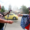 Pepperell resident Kevin Zappelli gives Roxann Chamberlain,with the senior center, a cool mist, as she hands him a mini American Flag, during the 4th of July Parade. Nashoba Valley Voice Photo by David H. Brow