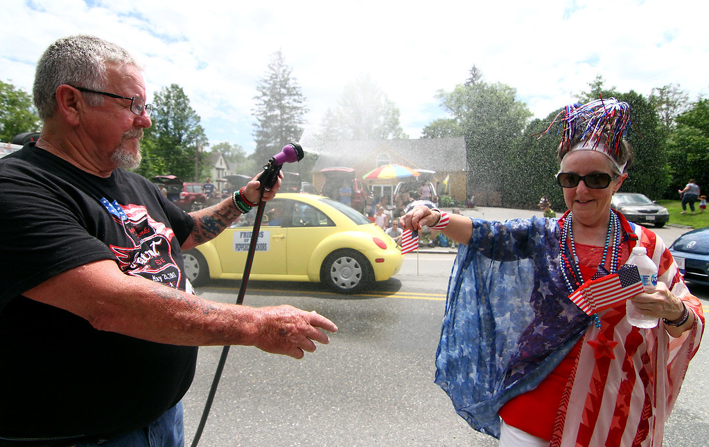 . Pepperell resident Kevin Zappelli gives Roxann Chamberlain,with the senior center, a cool mist, as she hands him a mini American Flag, during the 4th of July Parade. Nashoba Valley Voice Photo by David H. Brow