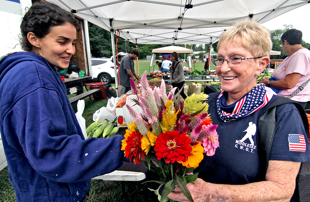 . Spiczka Farm staff worker Nancy Chaney sells a bunch of flowers to Sue Dow at the Pepperell Farmers Market. SUN/David H. Brow