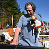 Kevin O'Clair of Pepperell holds his dog Lucy as he browses items at Pepperell's annual town wide yard sale held at the Town Field on Saturday morning.  SENTINEL & ENTERPRISE JEFF PORTER
