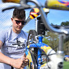 Patrick Goguen of Worcester helps with bike tune up's as buyers walk away with their new bikes during Pepperell's annual town wide yard sale held on the Town Field on Saturday morning.  SENTINEL & ENTERPRISE JEFF PORTER