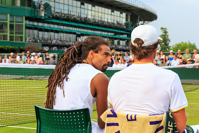 German tennis players Dustin Brown and Mischa Zverev talk tactics during a men's doubles match at the Wimbledon Tennis Championships 2017, All England Lawn Tennis and Croquet Club, UK