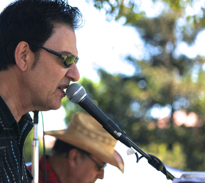 "Bandleader Tim Buley elected to ""channel"" Johnny Cash for an appreciative crowd at the third annual Camarillo Country Music Festival and Chili Cookoff with his rendition of ""Folsom Prison Blues"".<br /> Tim Buley Band member Bill Flores (background) took a solo on slide guitar."