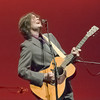 Jon Brion singing with an acoustic guitar.