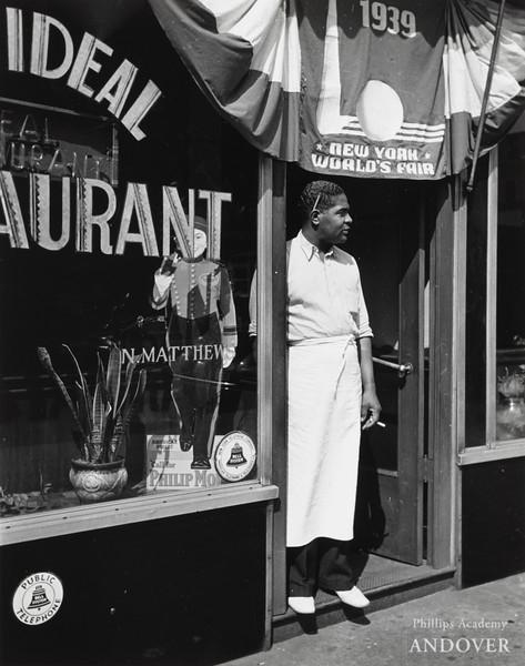 Lucien Aigner, Harlem restaurant owner standing under 1939 NY World's Fair poster, 1939. Gelatin silver print, 13 3/8 × 10 9/16 in. (34 × 26.8 cm)