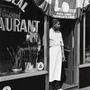 Lucien Aigner, Harlem restaurant owner standing under 1939 NY World's Fair poster, 1939. Gelatin silver print, 13 3/8 × 10 9/16 in. (34 × 26.8 cm)