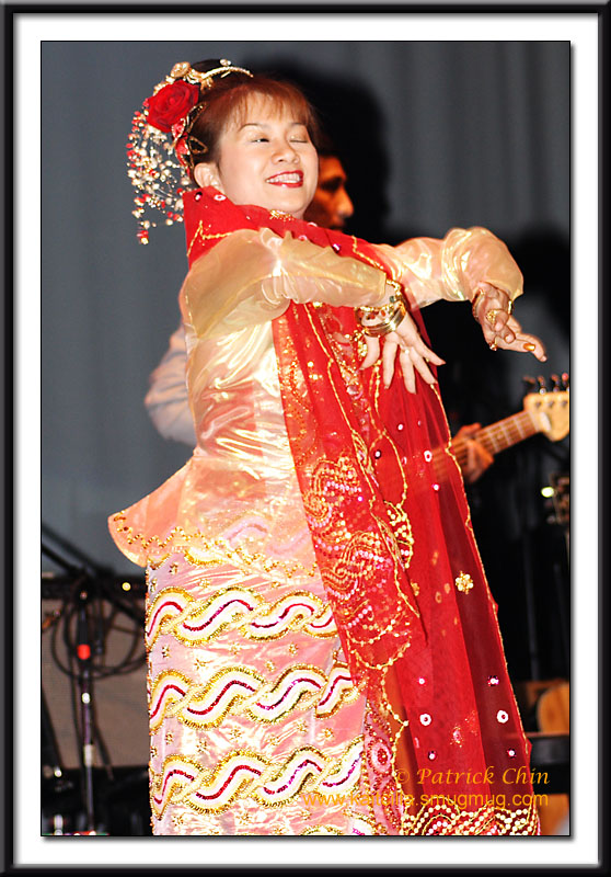 A Burmese lady performs Burmese folk dance wearing traditional Burmese dance costume.
