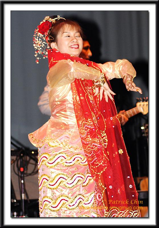 A Burmese lady performs Burmese folk dance wearing traditional Burmese dance costume.