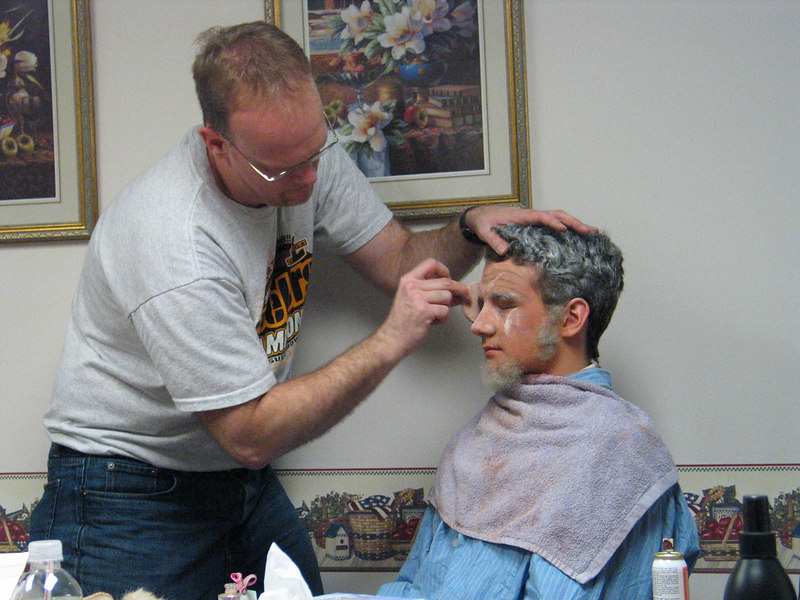 Darren Litz applies makeup to Joe Hy who plays Professor Digory and Father Christmas.