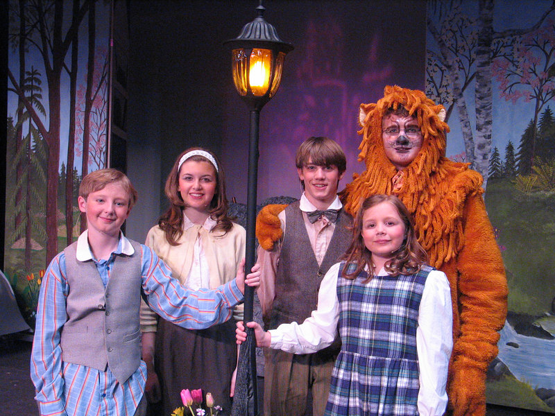 Edmunc, Susan, Peter, Lucy and Aslan by the lampost in the magical land of Narnia.