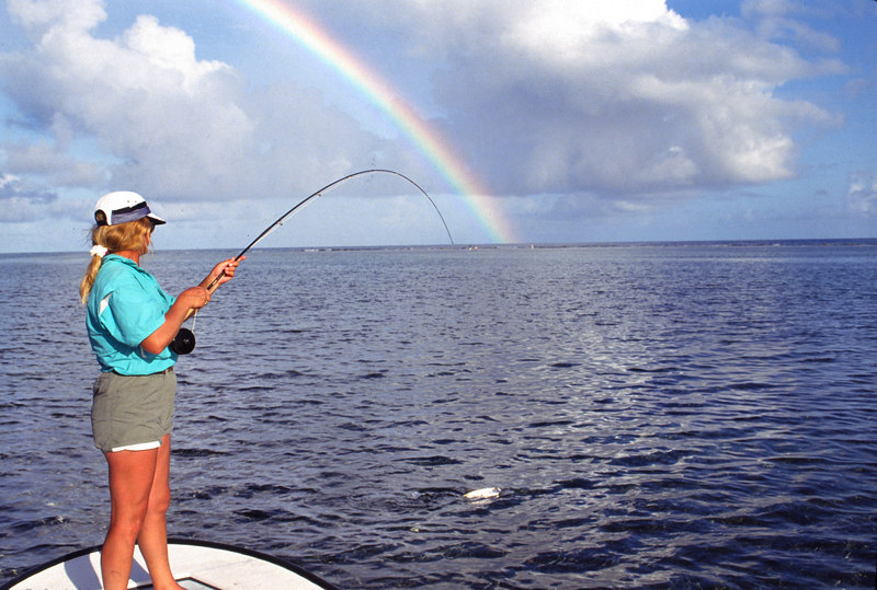 Wendy Gunn Landing a Bonefish with Rainbow Fly Fishing Turneffe Belize