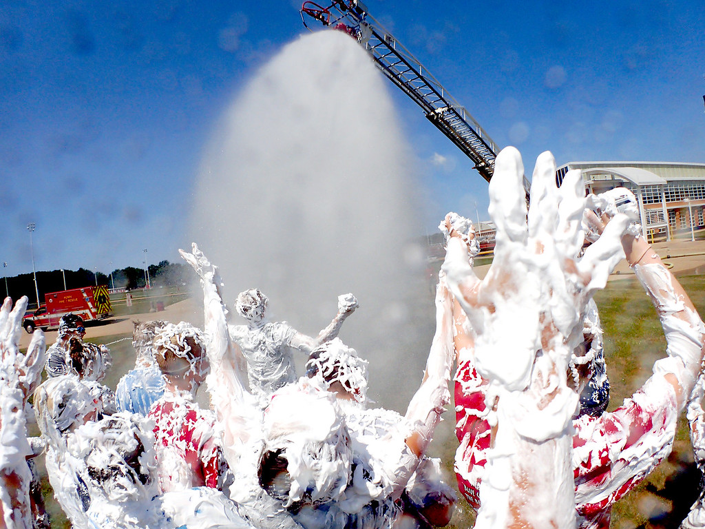 . Jonathan Tressler � The News-Herald <br> Perry High School Marching Band members welcome the water July 27 as a Perry Joint Fire District ladder truck sprays them off following their traditional Shaving Cream Showdown, which marks the end of the summer�s two-week band camp.