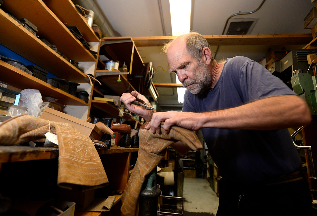 . Co-owner George Perry works to repair a pair of boots for a customer at Perry\'s Shoe Shop on Friday in Boulder. For more photos of the shoe shop go to dailycamera.com Jeremy Papasso Staff Photographer Aug. 11, 2017