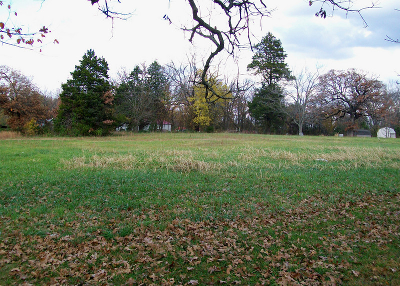 """This was once the softball field.  Home plate was behind the stone outhouse which has now been removed.  Also gone are the swings and slide. A small wooden well house has replaced the larger, stone one which was """"base"""" for playing hide and seek."""