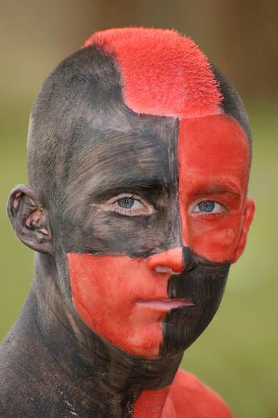 Stock image of an very colorful American  teenage boy painted with red and black body paint and sporting a  Mohawk haircut in support of his high school team