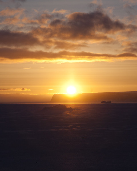 Sunset from the coast over sea ice and icebergs