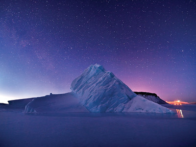 An iceberg, trapped in sea ice, with the 2am twilight (left) and the lights from Thule AFB (right). Thule, Greenland
