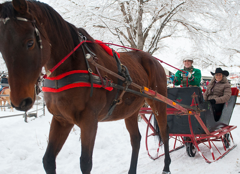 Founder Barbara Frodsham and volunteer Jayna Cadden ride in a open slay to bring holiday sprit to needy families.  In Farmington. On December 21 2013.(Brian Wolfer Special to the Standard-Examiner)