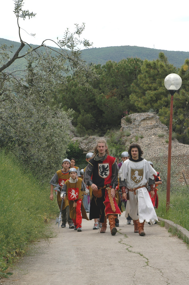a procession of children in mediaval dress, about to do (play) battle with each other in San Gimignano