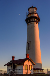 Lighthouse at sunset with half moon