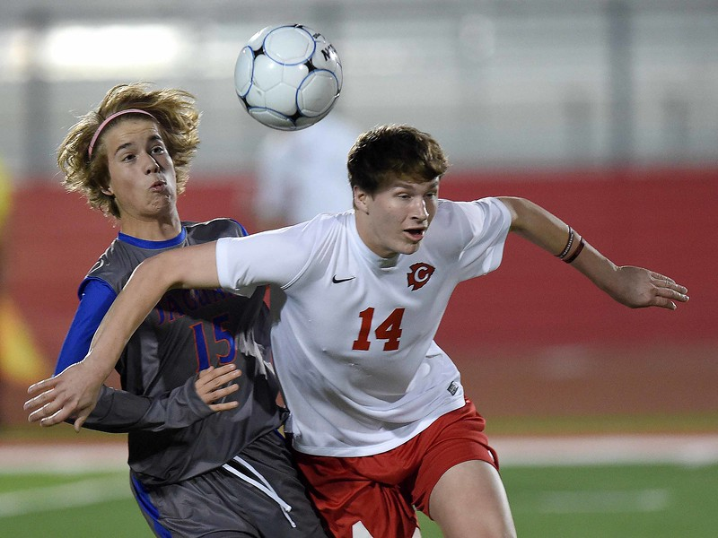 Clinton's Tucker Barefoot (14) and Madison Central's Christian Berry (15) battle for a ball near midfield on Tuesday, January 24, 2017, in the first round of the MHSAA Class 6A playoffs at Clinton High School in Clinton, Miss.