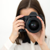 Woman photographer with camera over gray background