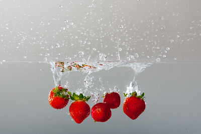 Strawberries splashing into the water