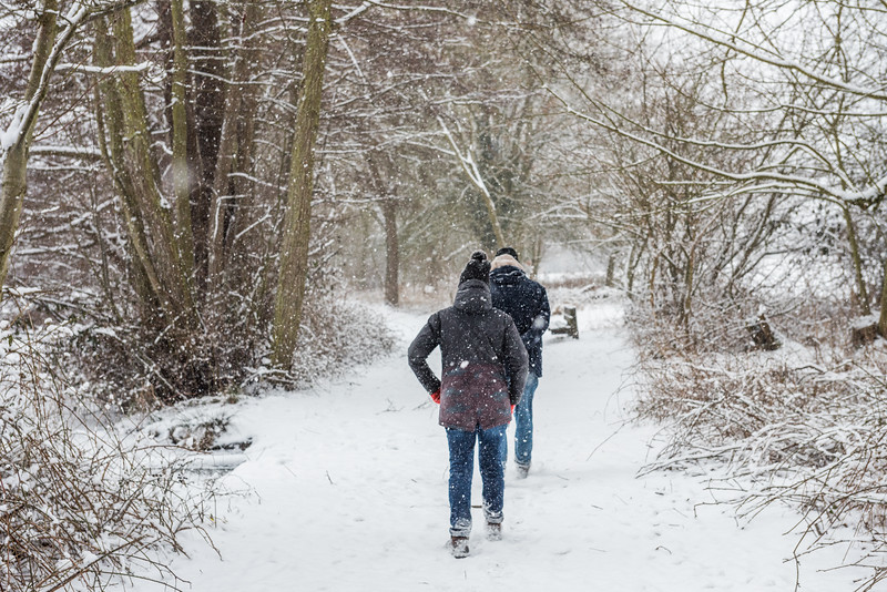 A couple walk in the snow at South Weald Country Park, Essex, England 28 February 2018