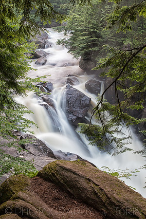Auger Falls. GPS Coordinates: ( 43.4668776, -74.2510587 ) This 40 foot falls is at the beginning of a series of drops, plunges and cascades totaling over 100 feet though this narrow gorge lined with Hemlocks on the Sacandaga River. Many potholes can be seen along the edge of the gorge when the water level is low. Please be careful around the falls area, as the banks are steep and slippery.